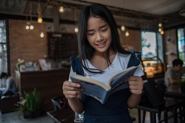 Young woman reading book sitting indoor in urban cafe. Free Photo
