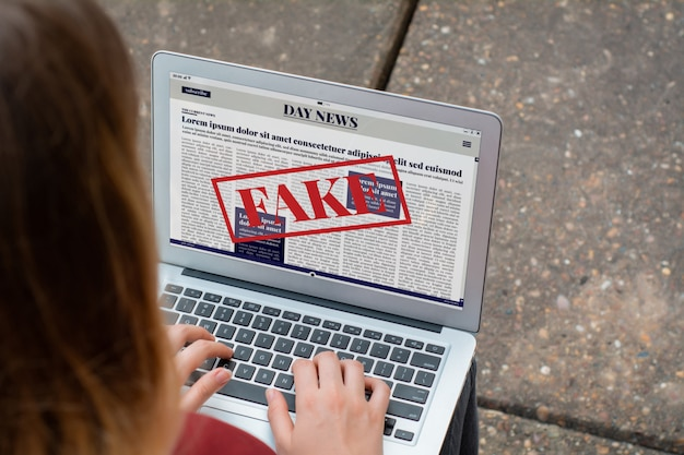 Young woman reading digital fake news on laptop Premium Photo