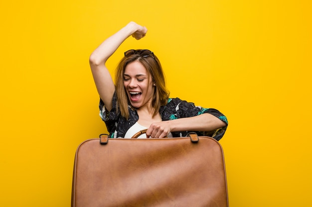 Young woman ready to go to vacation over yellow background Premium Photo