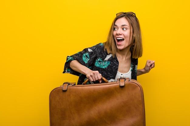 Молодая женщина готова отправиться в отпуск на желтом Premium Фотографии