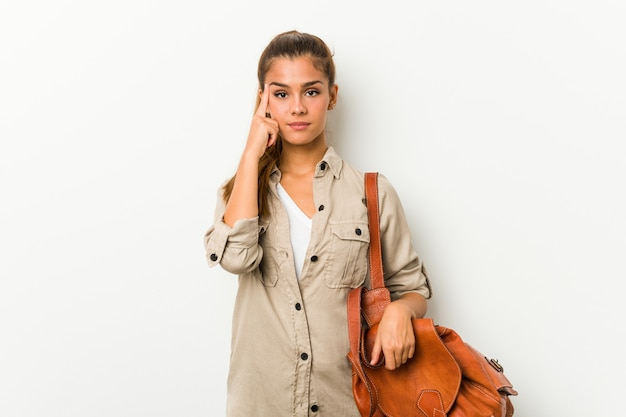 Young woman ready for a travel pointing temple with finger, thinking, focused on a task Premium Photo