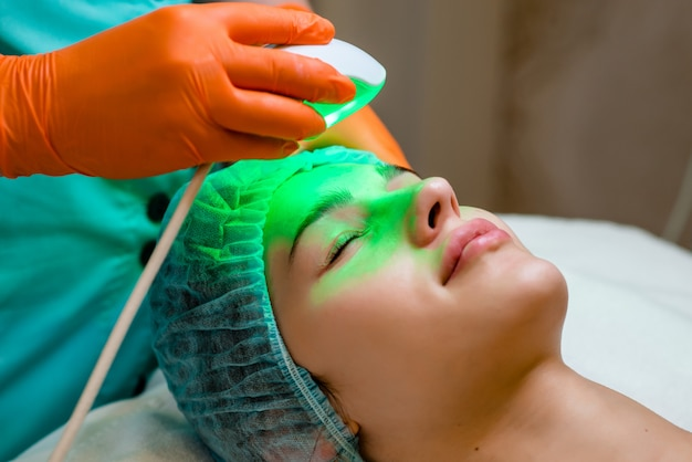 Young woman receiving epilation laser treatment on face at beauty center. Premium Photo