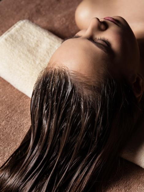 Giovane donna che riceve procedura di cura dei capelli nel salone della stazione termale. trattamento di bellezza. salone della stazione termale Foto Gratuite