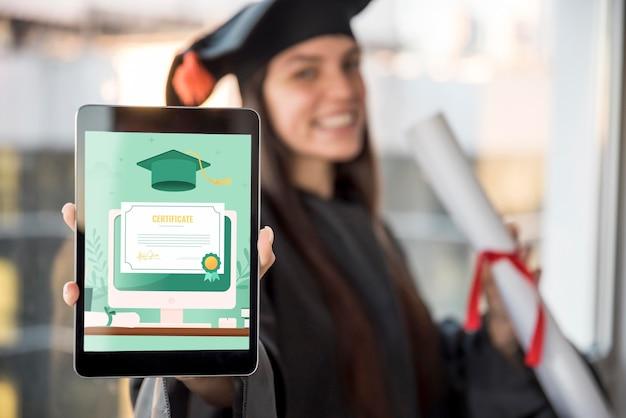 タブレットで彼女の卒業証書を受け取る若い女性 Premium写真