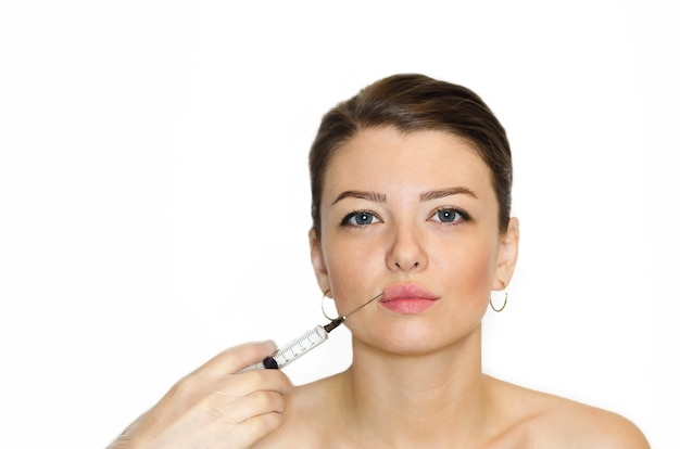 Young woman receiving injection of filler, botox in lips for augmentation. Premium Photo