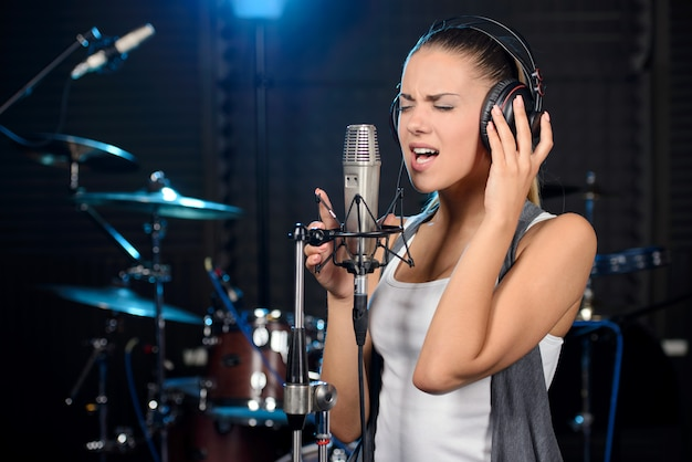 Young woman recording a song in a professional studio Premium Photo