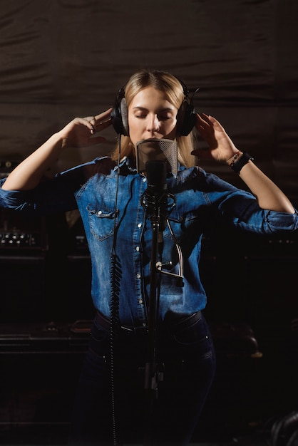 Young woman in recording studio talking into microphone. Premium Photo