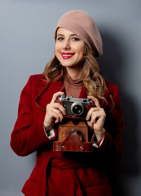 Young woman in red coat with photo camera Premium Photo