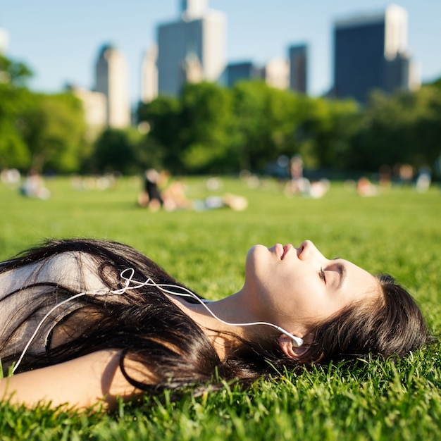 Young woman relaxing in central park laying on the grass and listening to music. new york city. Premium Photo