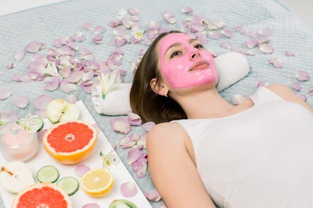 뷰티 살롱-실내 얼굴에 핑크 진흙 화장품 마스크와 함께 침대에서 편안한 젊은 여자. 소녀 주위의 꽃잎, 레몬, 자몽, 키위, 사과 조각 프리미엄 사진