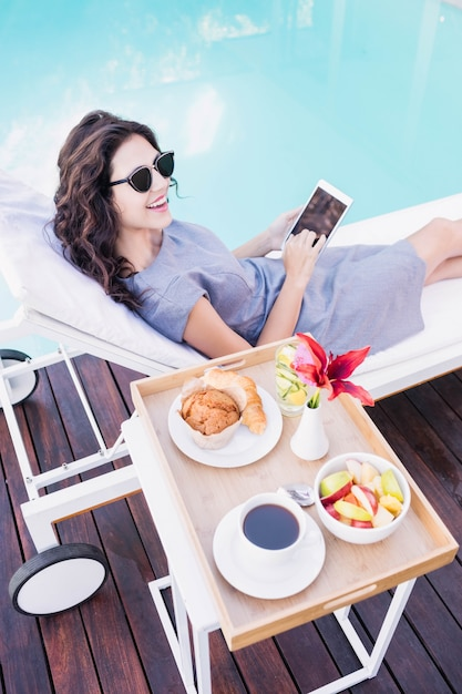 Young woman relaxing on a sun lounger and using smartphone near poolside Premium Photo