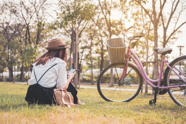 Young woman relaxing and using smart phone and surf internet in the park Premium Photo