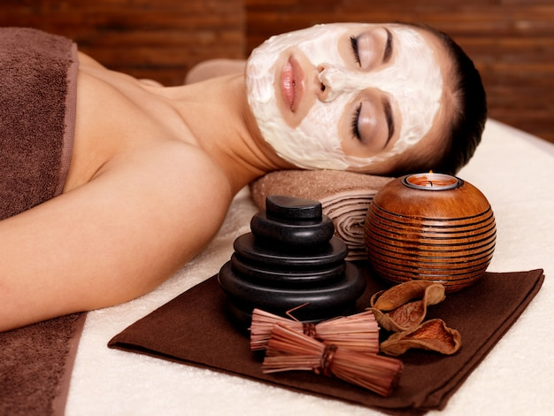Young woman relaxing with cosmetic mask on face at beauty salon- indoors Free Photo