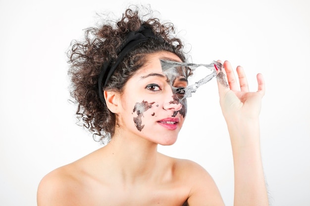 Young woman removing black face mask against white background Free Photo