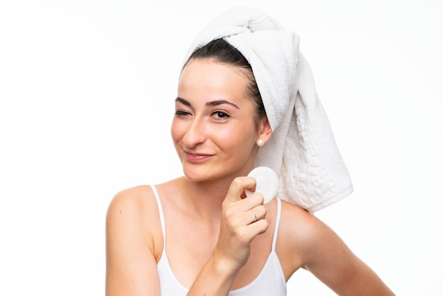Young woman removing makeup from her face with cotton pad Premium Photo