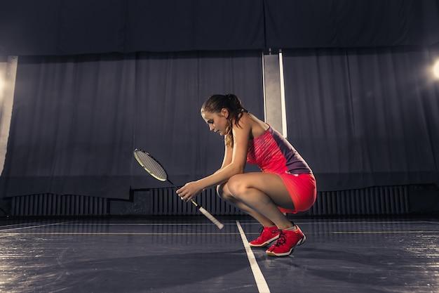 Молодая женщина отдыхает после игры в бадминтон в тренажерном зале Бесплатные Фотографии