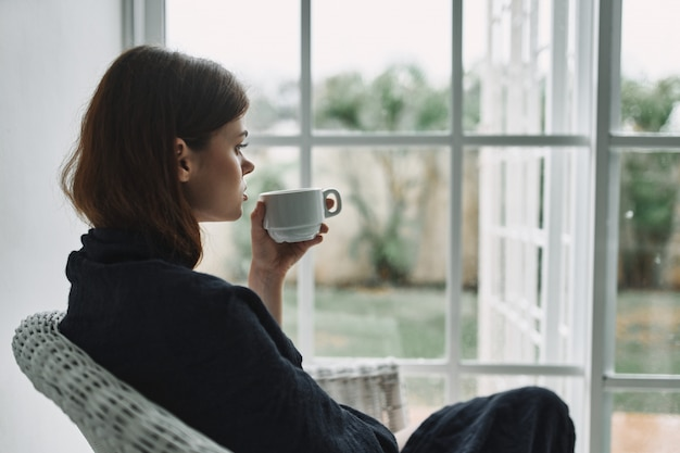 Young woman resting on armchair at home by the window Premium Photo