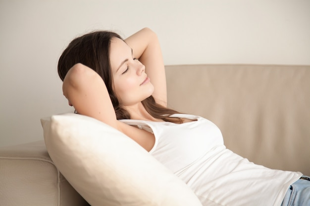 Young woman resting on comfortable sofa at home Free Photo