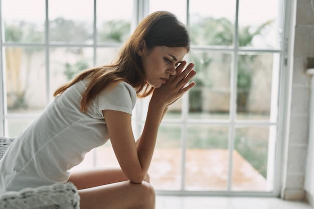 Молодая женщина отдыхает на кресле у окна дома Premium Фотографии