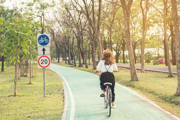 Young woman riding bicycle on bike lane in the park Premium Photo