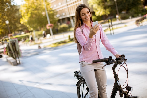 Young woman riding an electric bicycle and using mobile phone in urban environment Premium Photo
