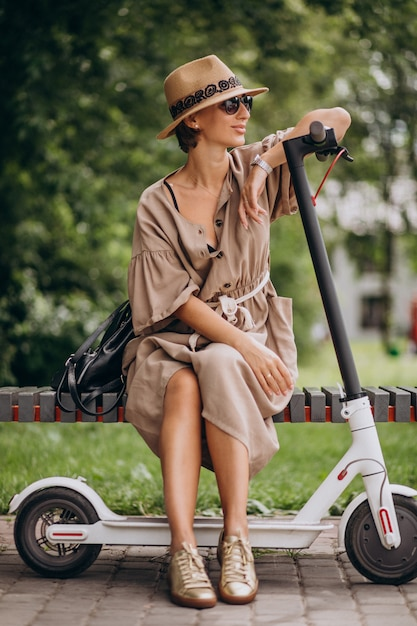 Young woman riding scooter in park sitting on bench Free Photo