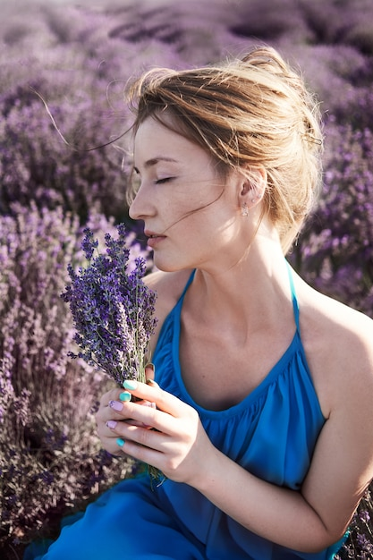 Young woman in the romantic blue dress relax in lavender fields. romantic girl dreams in lavender flowers. florist picks flowers for bouquet Premium Photo