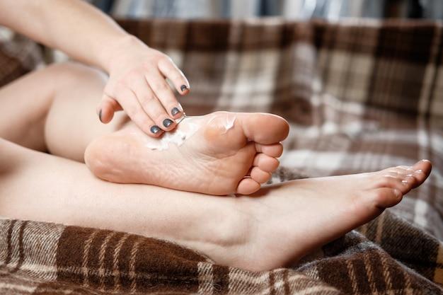 Young woman rubs cream on her feet Premium Photo