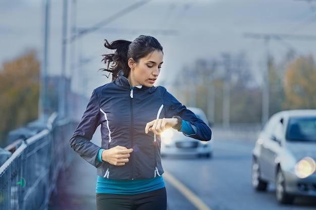 スマートウォッチから時間をチェックする若い女性ランナー Premium写真