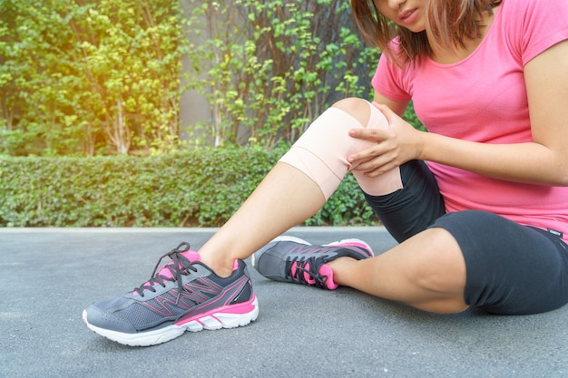 Young woman runner knee being applied bandage by herself in park. injury joint with fair. Premium Photo