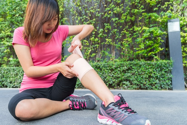 Young woman runner knee being applied bandage by herself in park. injury joint. Premium Photo