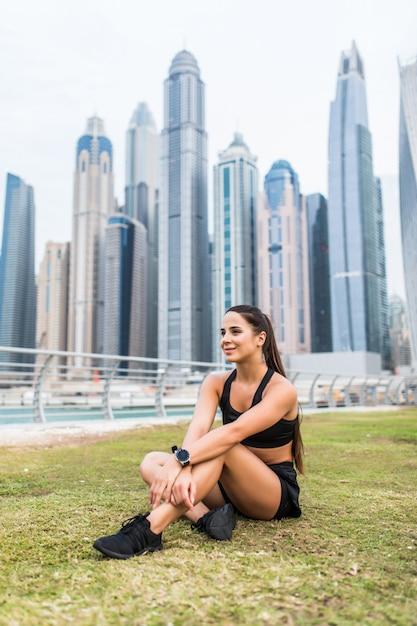 高層ビルの空間で屋外トレーニングの後休んで若い女性ランナー。トレーニングを休んでいる女性のジョガー。 Premium写真