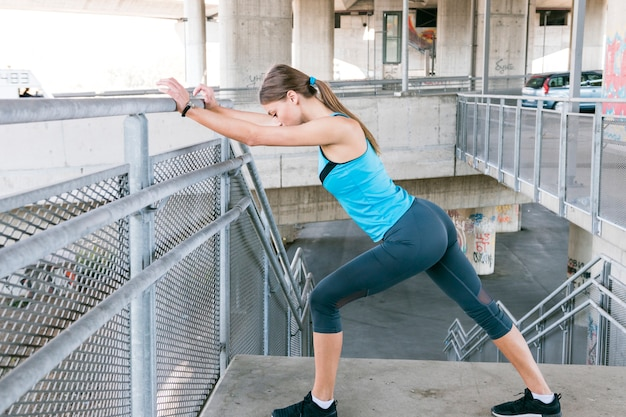 Young woman runner stretching legs before running Free Photo