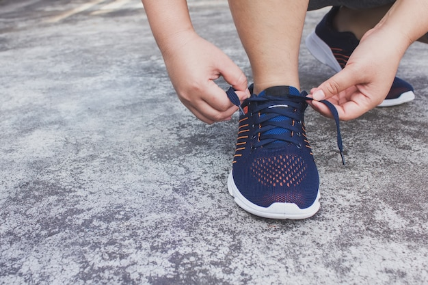 Young woman runner tying shoelaces Premium Photo