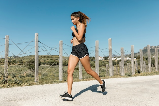 Young woman running along country road Free Photo