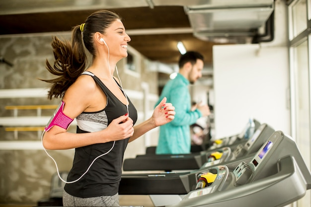 Young woman running on the treadmill and listening to music at the gym Premium Photo