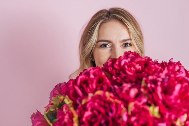 Young woman's face behind the beautiful roses bouquet against pink backdrop Free Photo