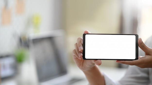 Young woman's hands holding blank screen of smartphone. Premium Photo