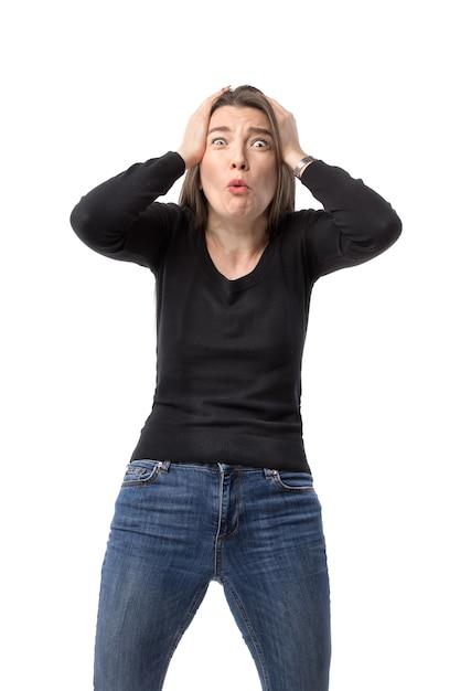 젊은 여자는 충격과 좌절의 표현으로 손에 그녀의 머리를 붙잡습니다. 프리미엄 사진