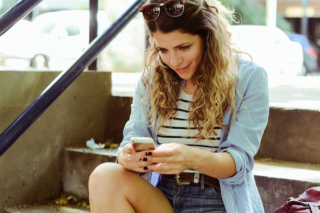 Young woman sending message with smartphone. Premium Photo
