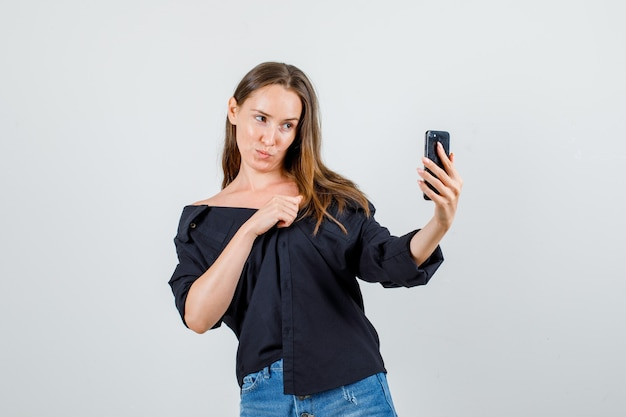 Free Photo Young Woman In Shirt Shorts Posing While Taking Selfie On Smartphone And Looking Cute