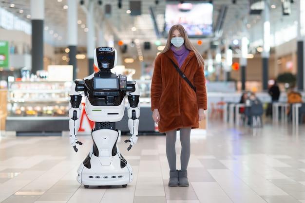 ストア内の若い女性の買い物客とロボットアドバイザー Premium写真