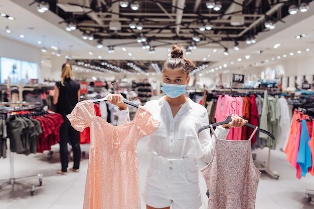 Giovane donna shopping abbigliamento in boutique di abbigliamento con maschera protettiva Foto Gratuite