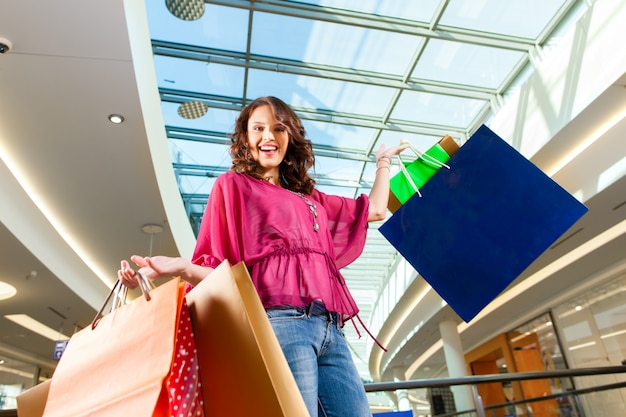 Young woman shopping in mall with bags Premium Photo