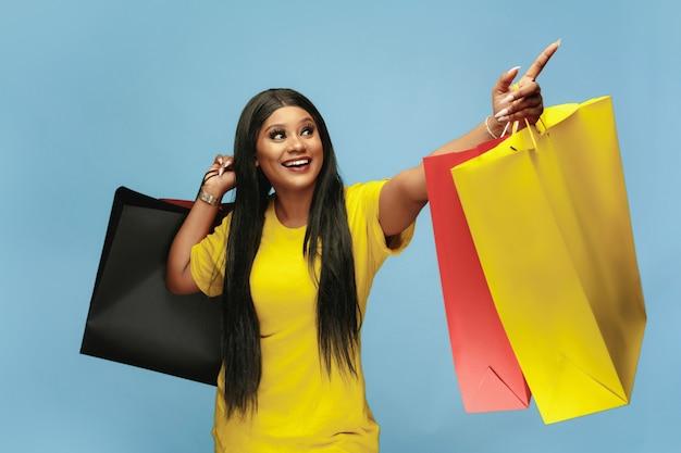 青い壁にカラフルなパックで買い物をする若い女性 無料写真