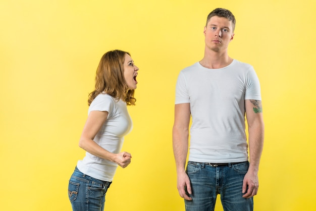 Young woman shouting on her boyfriend standing against yellow background Free Photo