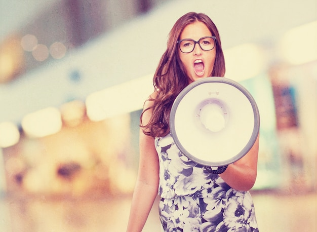 young woman shouting with megaphone Free Photo