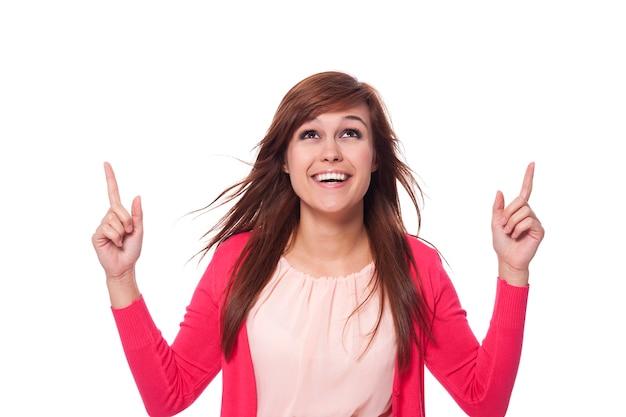 Молодая женщина показывает и смотрит на копию пространства Бесплатные Фотографии
