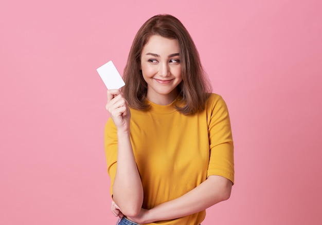 Young woman showing credit card and looking isolated over pink Premium Photo