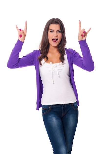 ハードロックの手サインを示す若い女性 無料写真